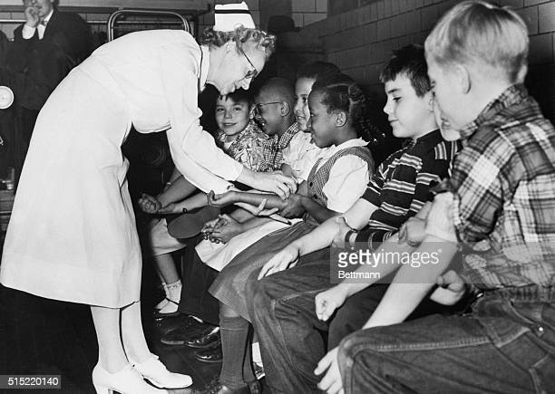 Nurse prepares children for a polia vaccine shot as part of a city-wide testing of the vaccine on elementary school students.