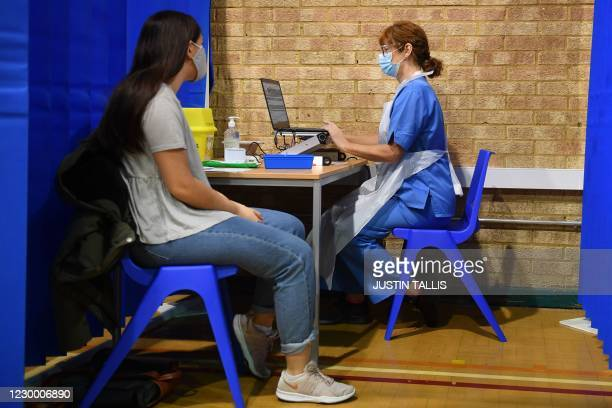 Nurse prepares to administer the Pfizer-BioNTech COVID-19 vaccine to a woman at a health centre in Cardiff, South Wales' on December 8, 2020. -...