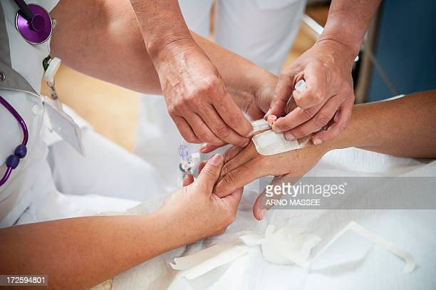 nurse preparing a patient for an iv line - iv drip womans hand stock pictures, royalty-free photos & images
