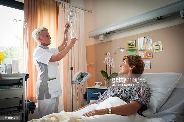nurse preparing iv drip - iv infusion stock photos and pictures