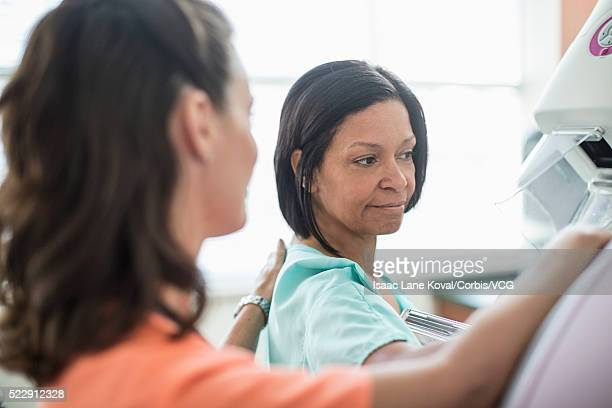 nurse preparing patient for mammography - mammogram stock pictures, royalty-free photos & images