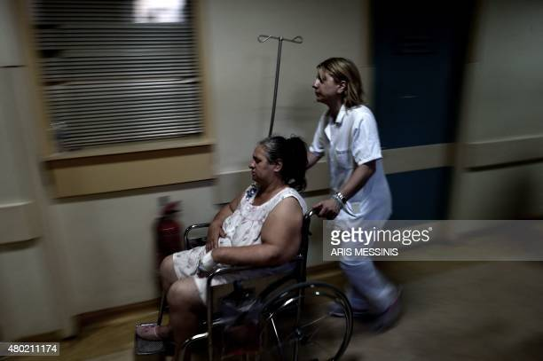 A nurse pushes a patient in a wheelchair in an Athens hospital on July 8 2015 With expectations of a Greek exit from the eurozone gathering pace...
