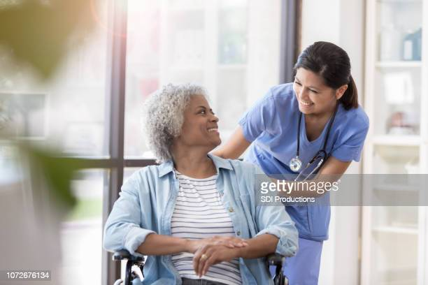 nurse pushes female patient in wheelchair - patient stock pictures, royalty-free photos & images