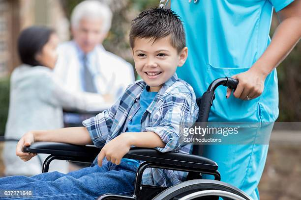 Nurse pushes happy young male patient in wheelchair