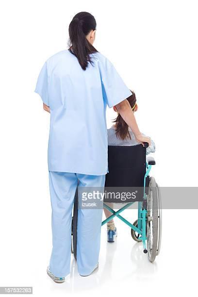 Nurse Pushing A Disabled Girl In Wheelchair, Studio Shot