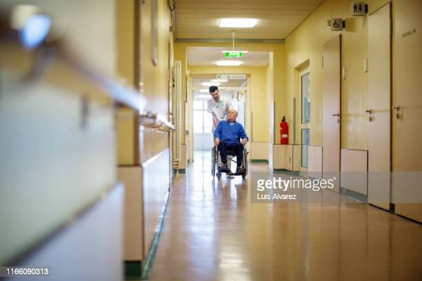 nurse pushing disabled patient in wheelchair - nursing assistant stock pictures, royalty-free photos & images