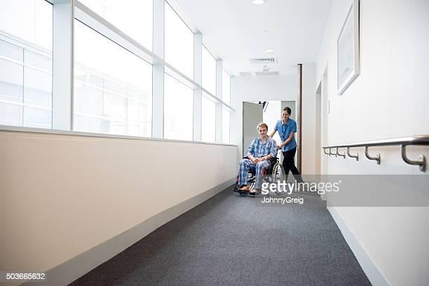 Nurse pushing patient along corridor in wheelchair