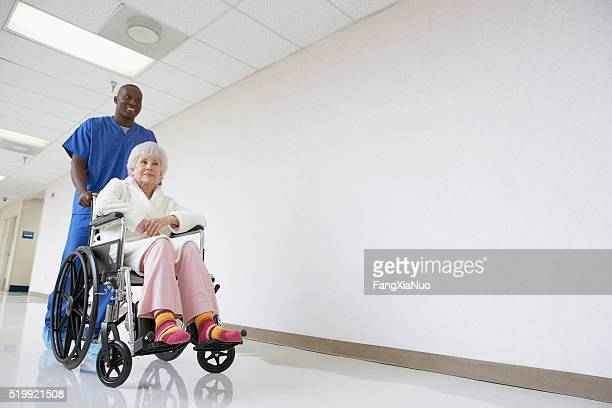 nurse pushing patient in a wheelchair - pushing stock pictures, royalty-free photos & images