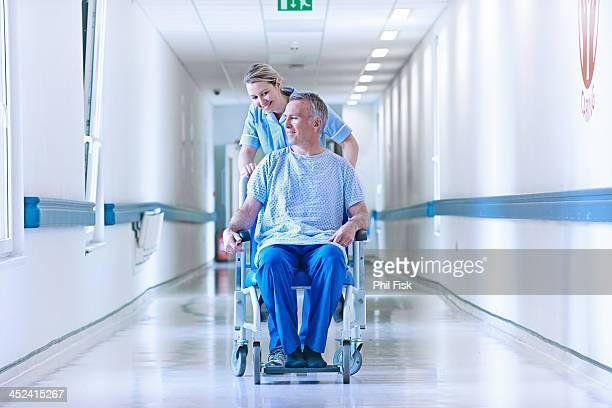 Nurse pushing patient in wheelchair down corridor
