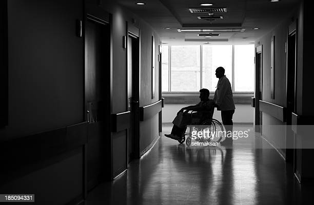 Nurse Pushing patient Sitting in Wheelchair in corridore