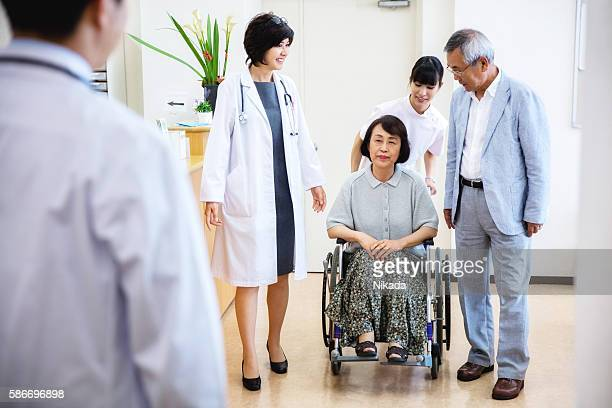 Nurse pushing senior woman sitting on wheelchair