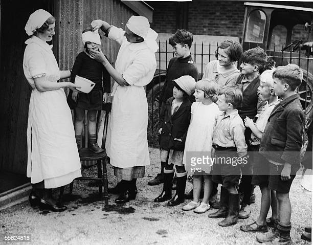 A nurse puts a bandage on the head of a hoppicking child as other ragged children watch with great interest Kent England September 12 1936 Until the...