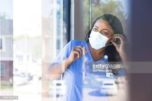 krankenschwester setzt auf schützende gesichtsmaske - essenzielle berufe und dienstleistungen stock-fotos und bilder