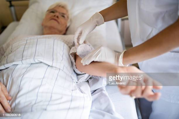 nurse putting a bandage on arm of senior patient - enfermera fotografías e imágenes de stock
