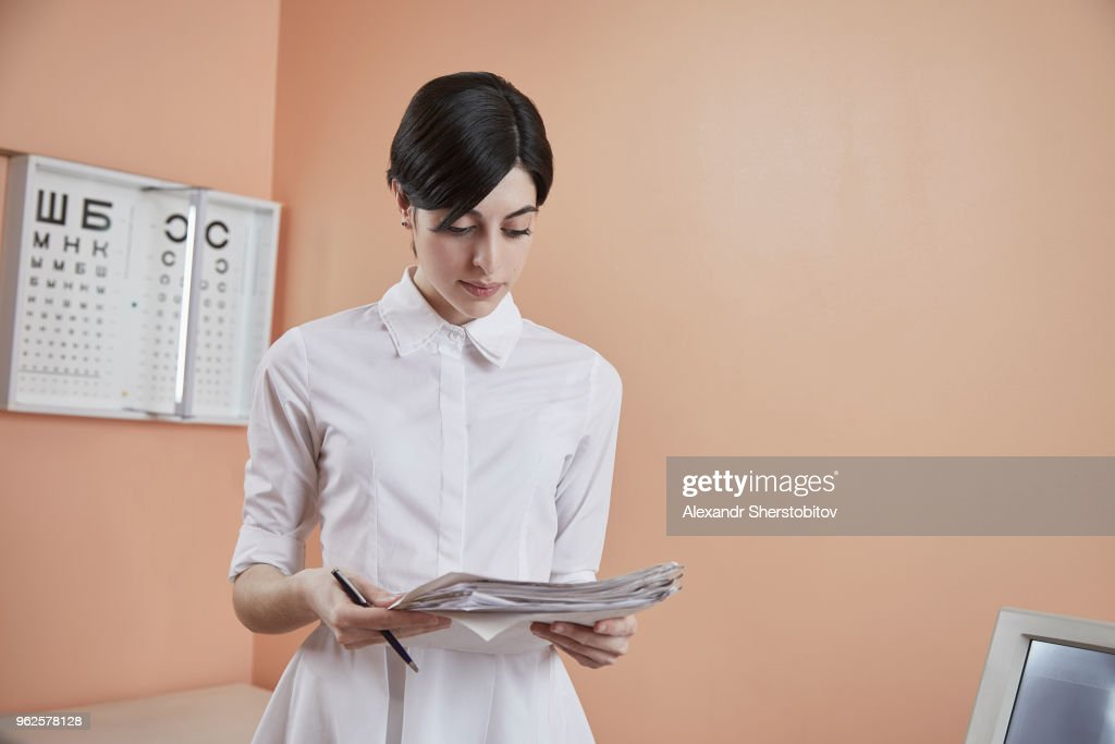 Nurse reading papers while standing in hospital : Stock Photo