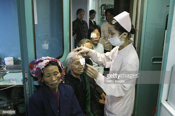 A nurse removes eye pads from patients one day after having their cataracts removed by a team of volunteer doctors on board the 'Lifetime Express'...