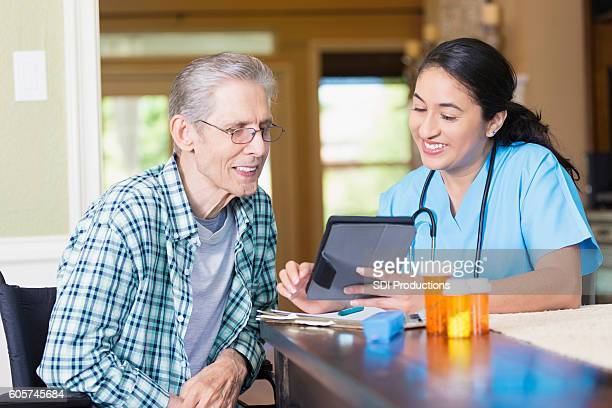 Nurse reviews senior patient's medical chart on digital tablet