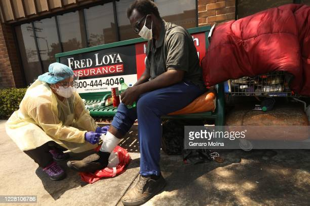 Nurse Richelle Legaspi, a member of the outreach team with The Center, helps bandage a wound Pookie Moores leg in East Hollywood on August 18,, 2020....