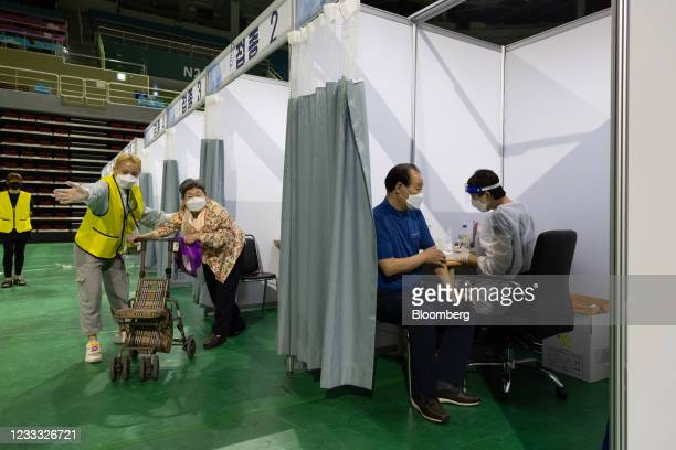 Nurse, right, prepares to administers a dose of the Pfizer-BioNTech Covid-19 vaccine at a vaccination site inside the Incheon Samsan World Gymnasium...
