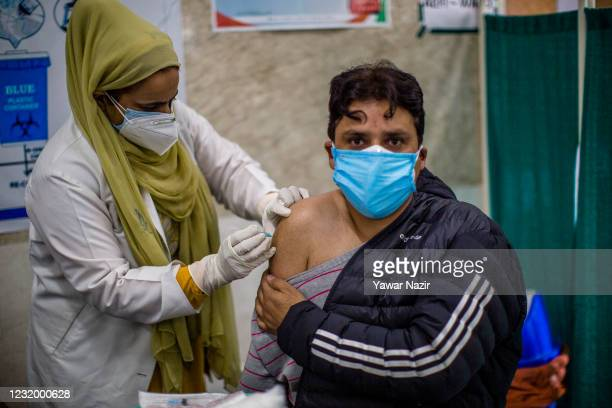Nurse Safina Shakeel, injects a dose of the Indian-made version of the Oxford/AstraZeneca vaccine, Covishield COVID-19 Vaccine to a Kashmiri man at a...