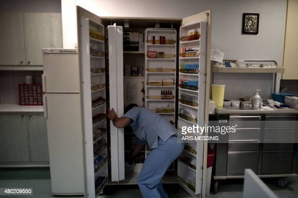 A nurse searches for medicine in an Athens hospital on July 7 2015 With expectations of a Greek exit from the eurozone gathering pace health...