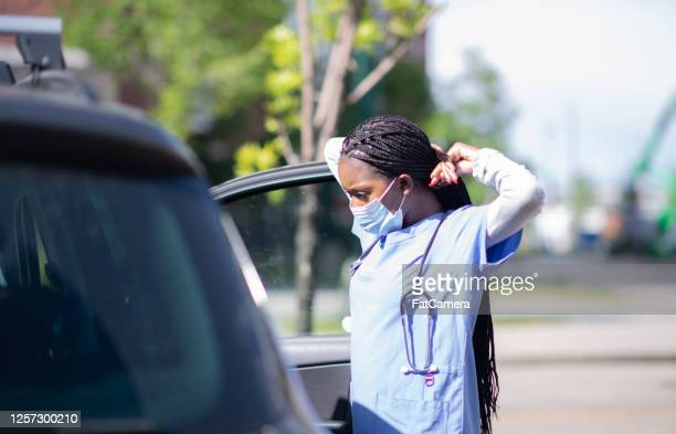 nurse secures mask at her car in parking lot - fatcamera stock pictures, royalty-free photos & images