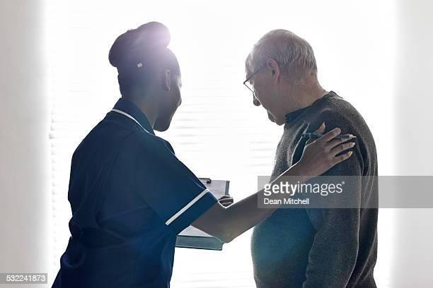 Enfermera mostrando informe médico con paciente senior en hospital