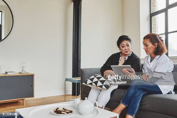 enfermera que muestra el informe médico a mujer senior en tableta digital - home carer fotografías e imágenes de stock