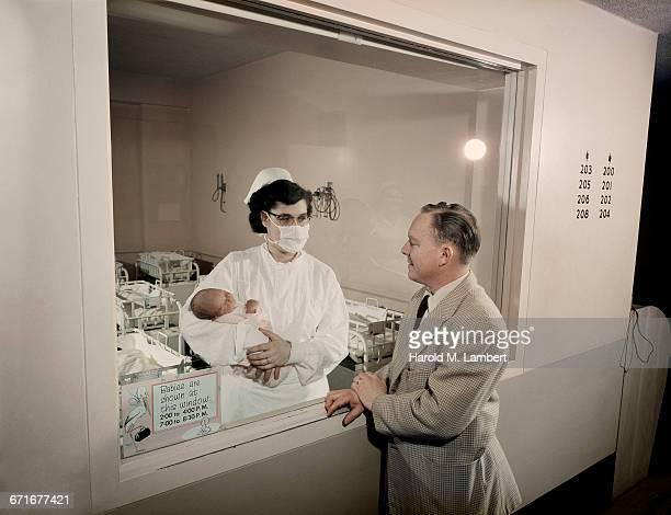 Nurse Showing Newborn Baby To Man
