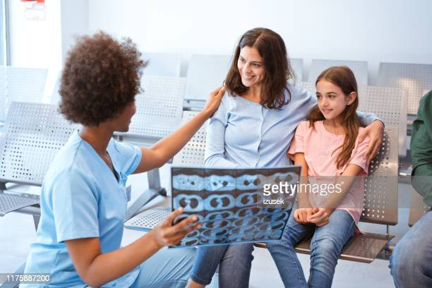 nurse showing x-ray to girl and her mother - izusek stock pictures, royalty-free photos & images