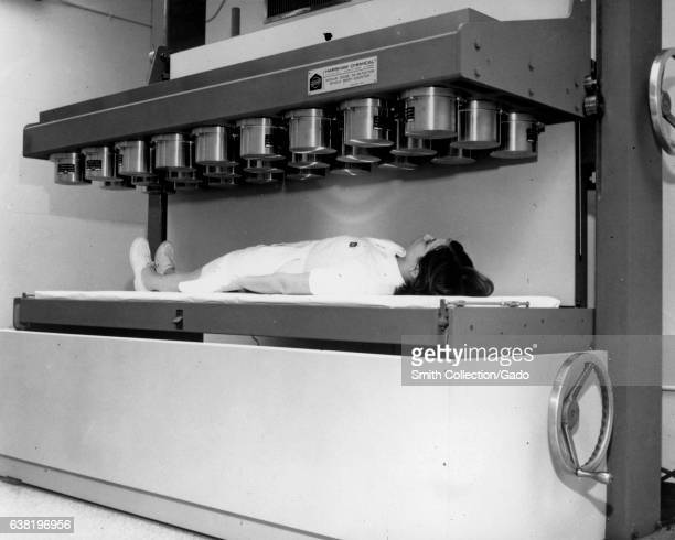 A nurse simulates a patient in the multicrystal low level whole body counting and gamma ray scanning spectrometer system 1968 Image courtesy US...