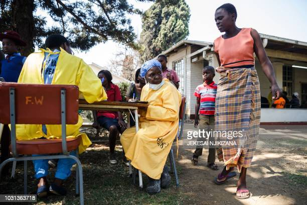 A nurse sits at a table as she takes care of cholera patients during a visit of Zimbabwe Minister of Health at the cholera treatment centre of the...