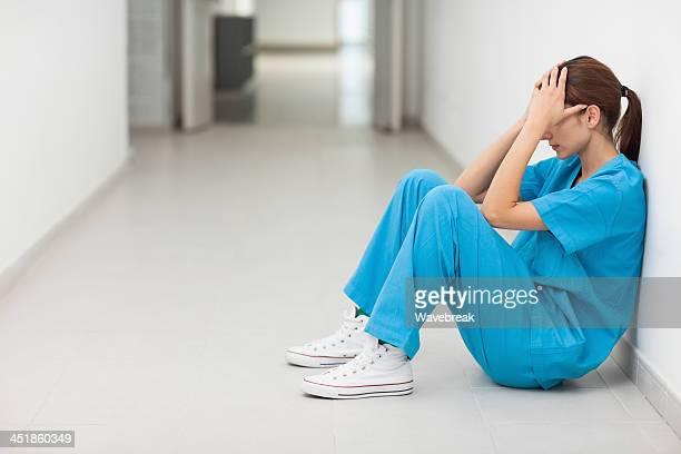 nurse sitting in a corridor while holding her head - overwerkt stockfoto's en -beelden