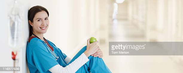 nurse sitting with apple in hospital corridor - one mid adult woman only stock pictures, royalty-free photos & images