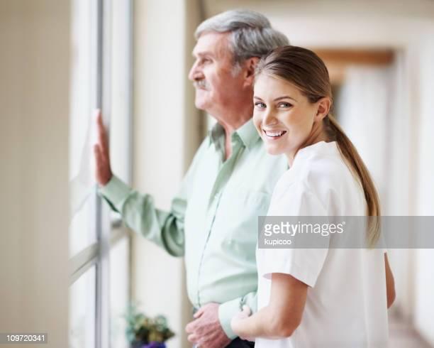Enfermeira sorridente enquanto o Idoso a olhar pela janela em hospital
