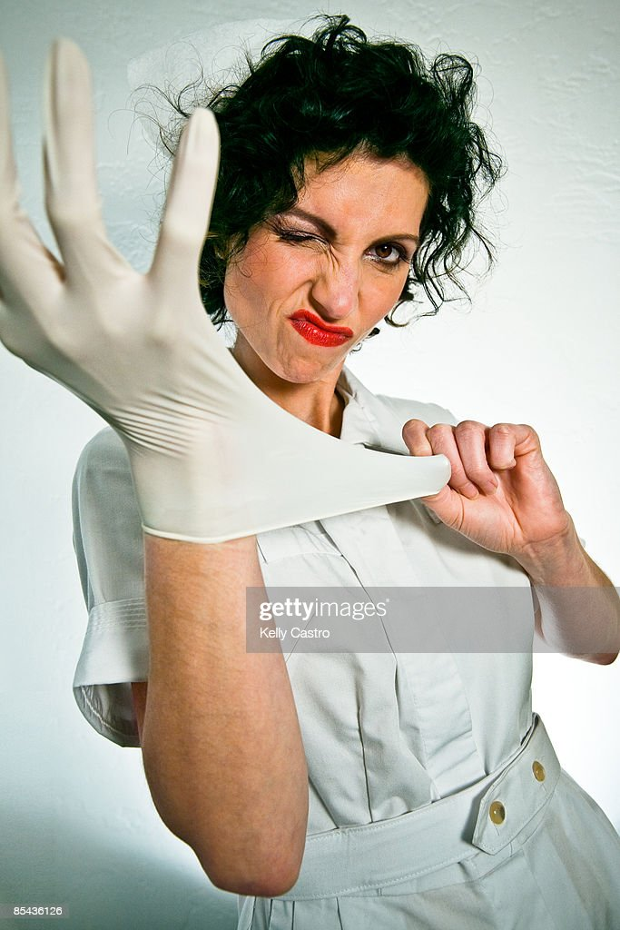 nurse snapping on rubber glove : Stock Photo