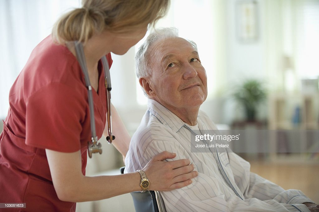 Nurse speaking to elderly man : Stock Photo