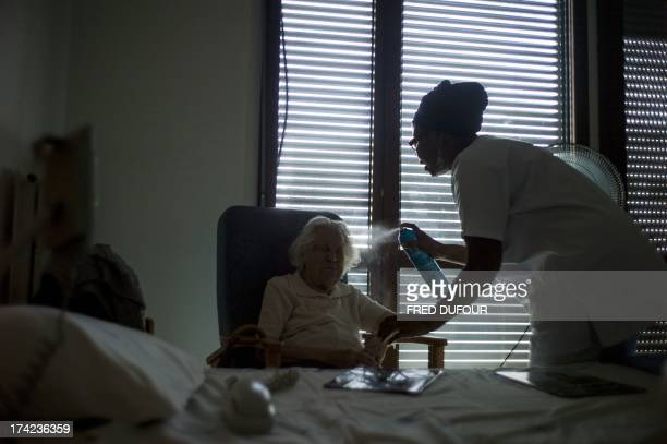 A nurse sprays water to cool off an old woman at the geriatric hospital of Argenteuil on July 22 2013 as France swelters under a summer heatwave AFP...