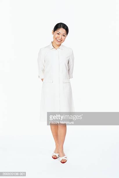 Nurse standing with hands behind back, smiling, portrait