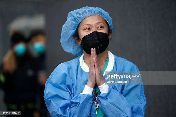 A nurse stands outside NYU Langone Hospital as people cheer to show their gratitude to medical staff during the daily Clap Because We Care initiative...