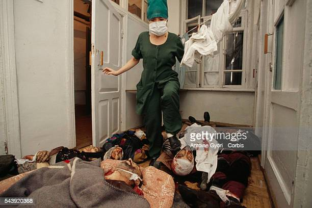 A nurse steps over corpses on the floor of the Grozny Hospital following a bomb attack by Russian jets on a busy market in the Chechen capital...