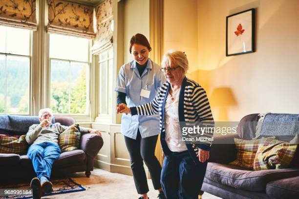 nurse supporting old woman to walk indoors - social services stock pictures, royalty-free photos & images