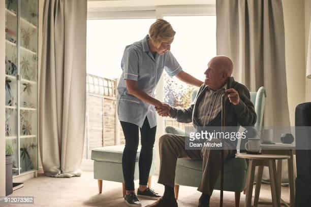 krankenschwester unterstützende senior patient zu hause - fotostock stock-fotos und bilder