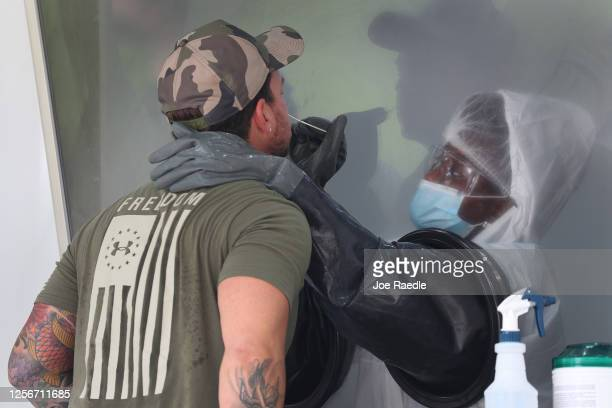 Nurse swabs the nose of Henry Brenlla through a glass pane in the Aardvark Mobile Health's Mobile Covid-19 Testing Truck on July 17, 2020 in Miami...