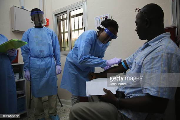 A nurse takes a blood sample from Emmanuel Lansana the first person to take part in the Ebola vaccine study being conducted at Redemption Hospital...