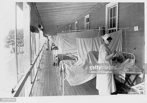 A nurse takes a patient's pulse in the influenza ward at Walter Reed Hospital Washington DC November 1 1918