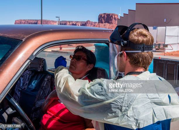 Nurse takes a swab sample from a Navajo Indian woman complaining of virus symptoms, at a COVID-19 testing center at the Navajo Nation town of...