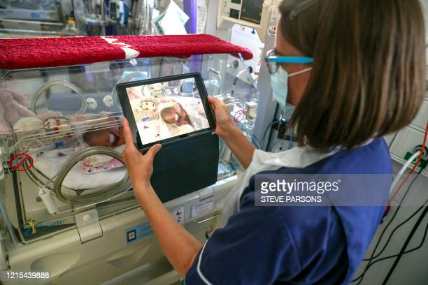 Nurse takes a video of a premature baby to send to the parents as visiting hours are restricted due to the Covid-19 virus in the maternity ward at...