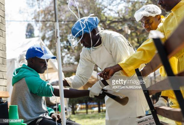A nurse takes care of a cholera patient during a visit of Zimbabwe Minister of Health at the cholera treatment centre of the Beatrice Infectious...