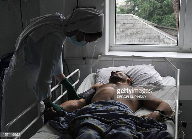 A nurse takes care of a terminally ill patient on July 6 2010 at an HIV/AIDS clinic in Kiev With an HIV prevalence rate of 111 percent among...